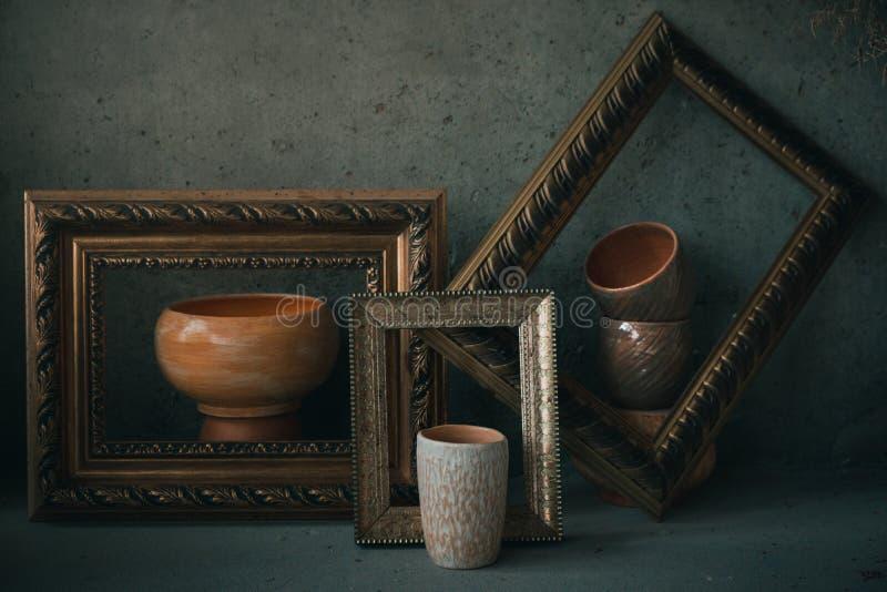 Чашки и шары взгляда со стороны керамические в картинных рамках как на картина стоковое фото