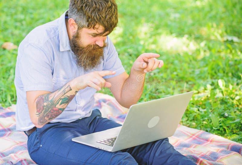 Человек бородатый с ноутбуком сидит предпосылка природы луга Писатель ища окружающая среда природы воодушевленности Воодушевленно стоковое изображение