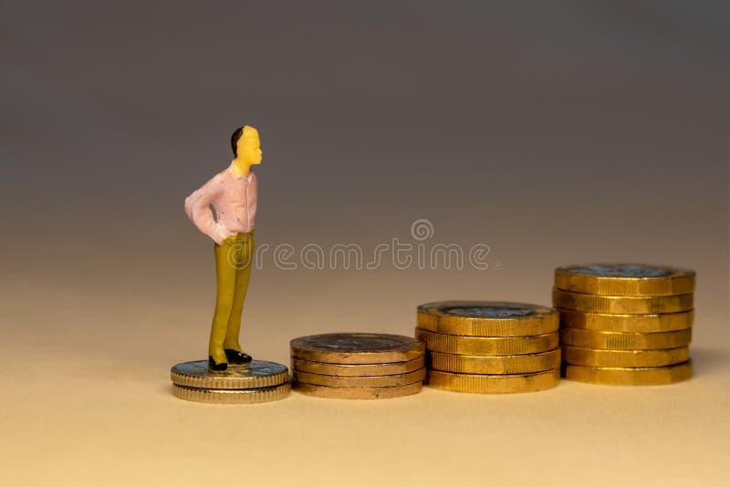 Человек взбираясь на увеличивая кучах золотых монет Сохраняя деньги для выхода на пенсию, карьеры дела или концепции вклада стоковое фото rf