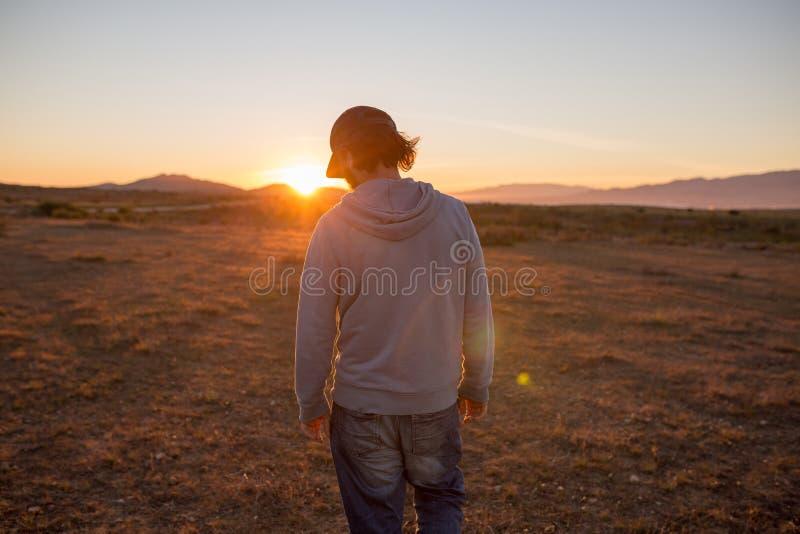 Человек в древнем ландшафте во время красивого пылая захода солнца стоковые фото