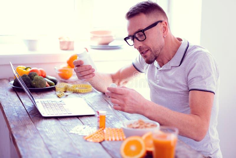 Человек водя сбалансированную диету держа его витамины утра имея здоровый завтрак стоковая фотография rf
