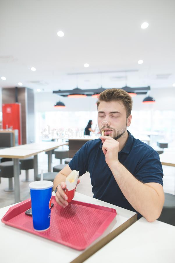Человек ест замороженные картошки с его закрытыми глазами и выпивает крутой напиток Насладитесь фаст-фудом стоковое изображение