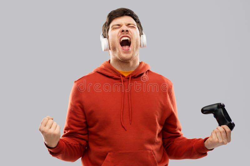 Человек или или gamer с gamepad выигрывая в видеоигре стоковое изображение