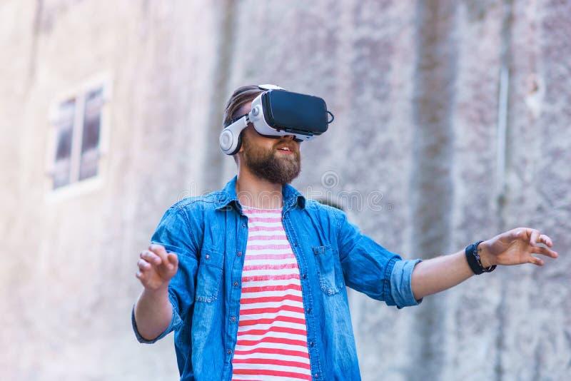 Человек идя в улицу в увеличенном шлемофоне реальности Виртуальная реальность и футуристическая концепция технологии стоковые изображения rf