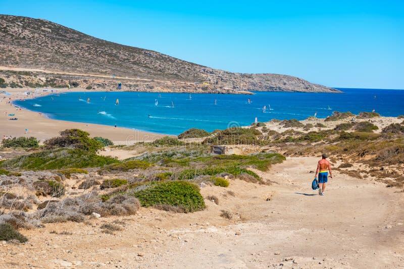 Человек идя к пляжу Prasonisi вполне windsurfers Родоса, Греции стоковые фото