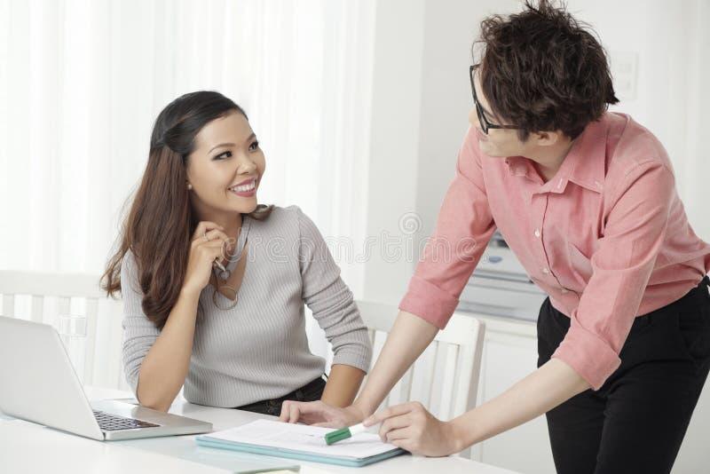 Человек и женщина Cheerfu сотрудничая в офисе стоковые фото
