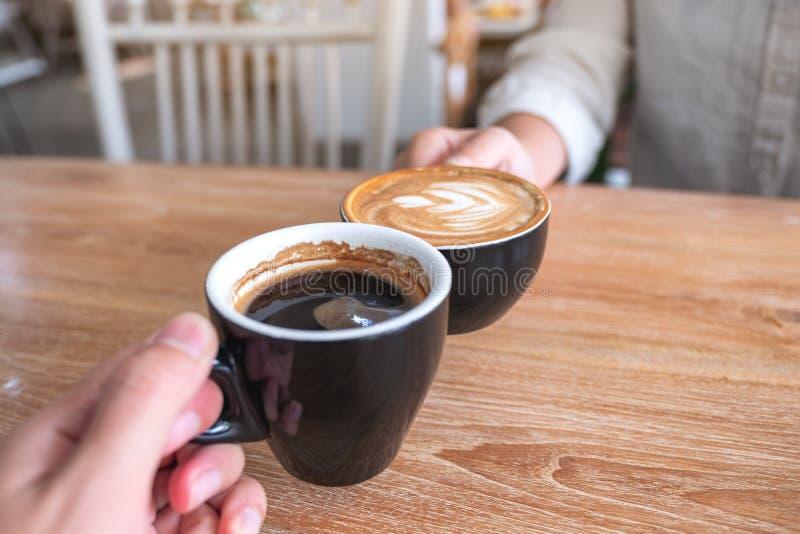 Человек и женщина clinking 2 кружки кофе на деревянном столе в кафе стоковая фотография