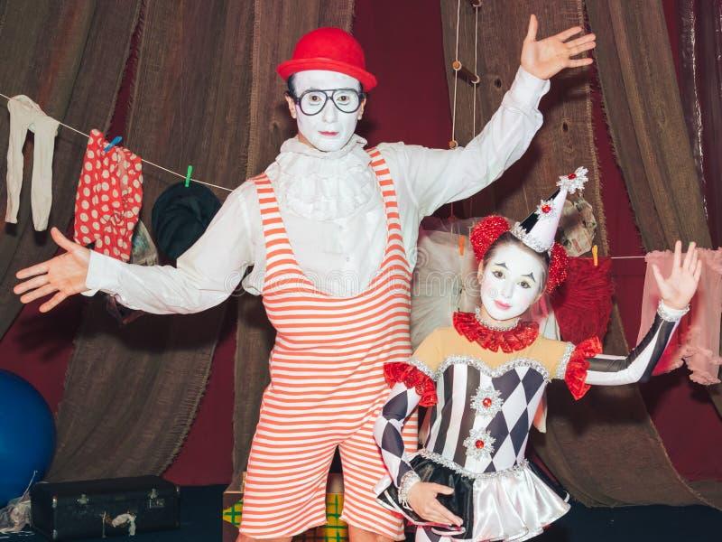 человек клоуна на коньках ролика с его маленькой ассистентской девушкой его персоны этапа стоковая фотография