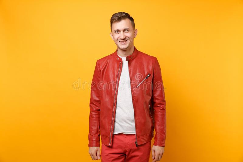 Человек моды портрета усмехаясь красивый молодой 25-30 лет в красной кожаной куртке, положение футболки изолированной на ярком стоковая фотография rf