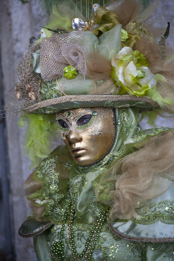 Человек нося маску Венеции и костюм зеленого цвета и золота на масленице Венеции в Венеции Италии стоковые изображения rf
