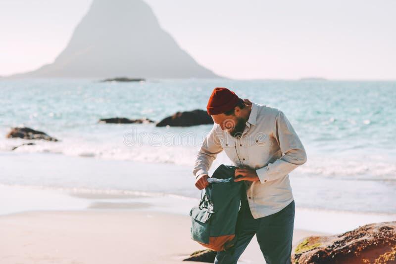 Человек пакуя его рюкзак на пляже моря путешествуя в Норвегии стоковые изображения
