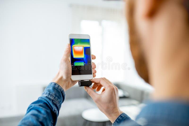Человек проверяя потерю тепла дома с камерой thermovision внутри помещения стоковые изображения rf