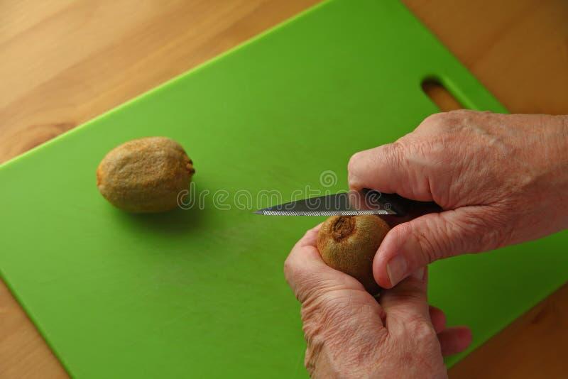 Человек подготавливает киви стоковое изображение