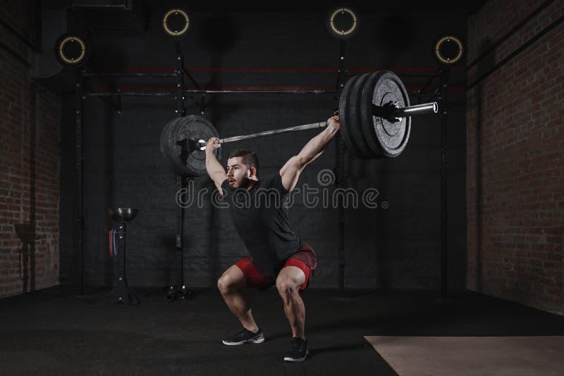 Человек делая сидения на корточках с тяжелыми накладными расходами штанги на спортзале Красивый человек практикуя функциональные  стоковое фото rf