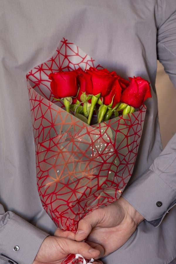 Человек держа букет красных роз стоковые изображения rf
