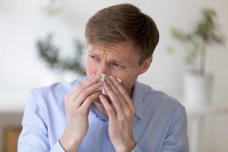 Человек держа бумажный носовой платок и дуя нос стоковая фотография