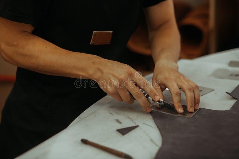 Человек держа производить инструмент и работу Закройте вверх мастера работая с кожаной тканью на его мастерской используя инструм стоковое фото