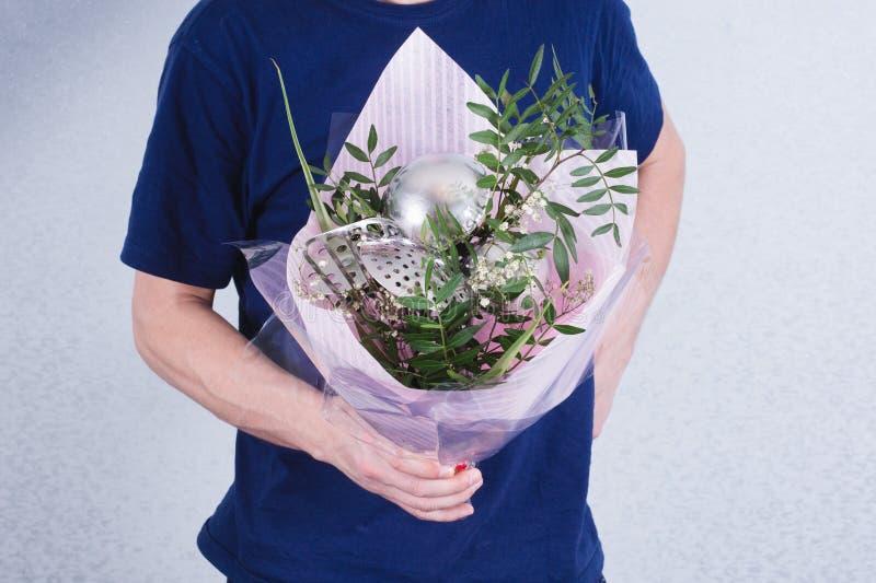 Человек держит букет цветков и ковшей концепция патриархального неравенства общества и рода Сексизм и феминизм стоковое изображение rf
