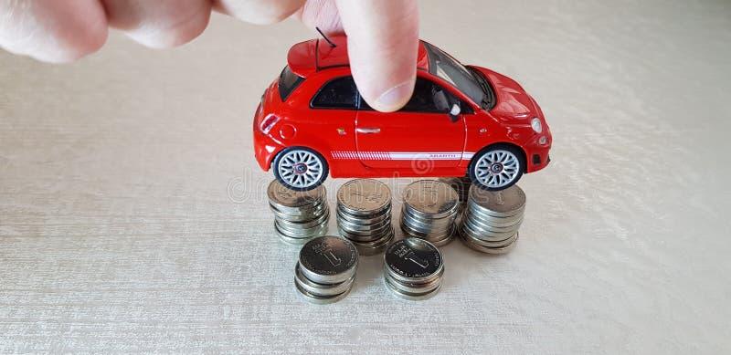 Человек держит в его игрушке abarth Фиат 500 пальцев красной над кучей монеток одного израильских шекеля стоя в столбцах стоковые изображения rf