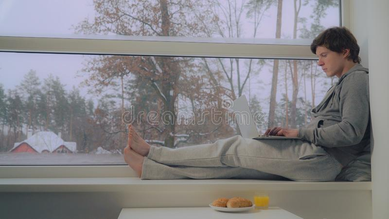 Человек сидя на компьтер-книжке пользы силла окна стоковые фотографии rf