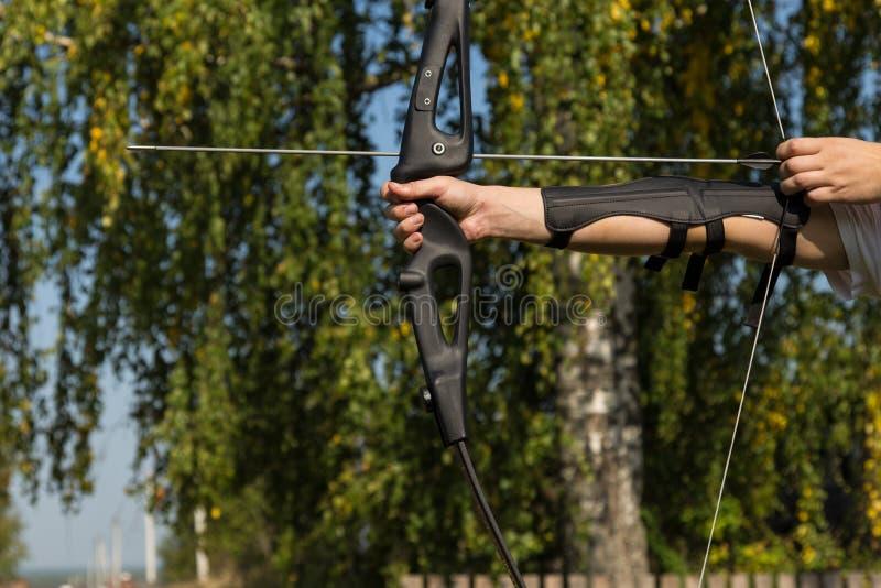 Человек снимает от смычка Конец-вверх Практика archery стоковое фото