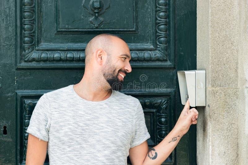 Человек с бородой звеня дверной звонок снаружи стоковое фото