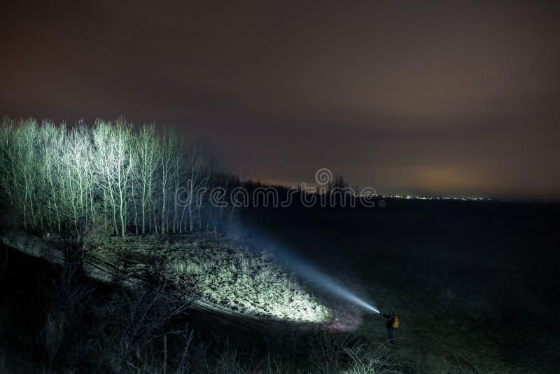 Человек с электрофонарем в лесе вечером стоковое фото rf