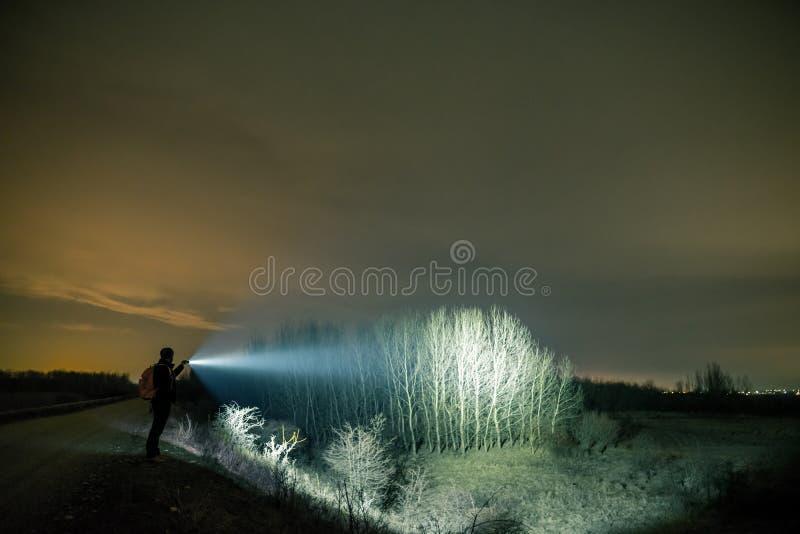 Человек с электрофонарем в на открытом воздухе вечером стоковое изображение rf