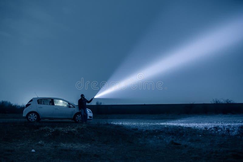 Человек с электрофонарем в на открытом воздухе вечером стоковые фотографии rf