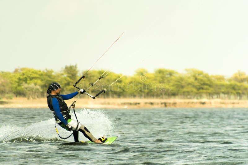 Человек фото действия Kitesurfing Kiteboarding среди волн быстро идет стоковые фото