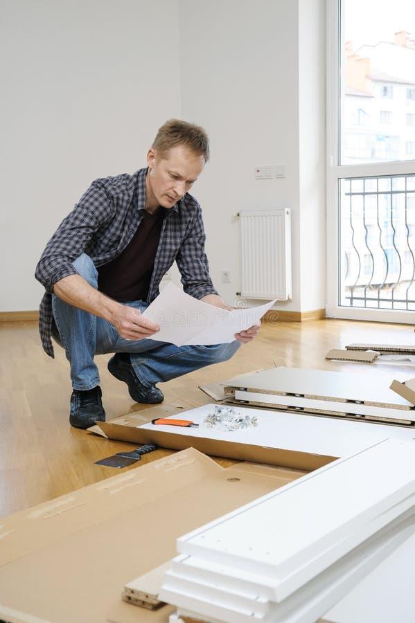Человек читает инструкции собрать мебель стоковое фото rf