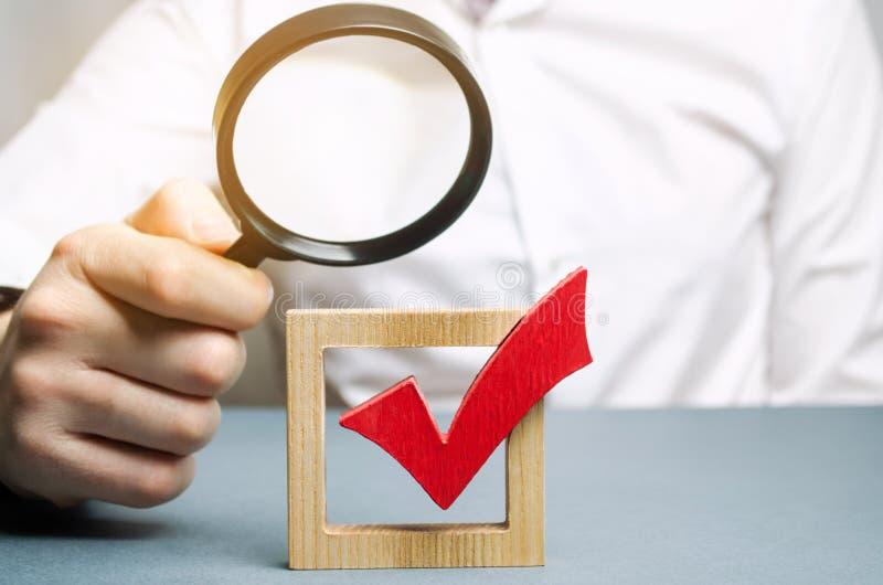 Человек рассматривает красную контрольную пометку через лупу Определять прозрачность легитимности избрания стоковое фото rf