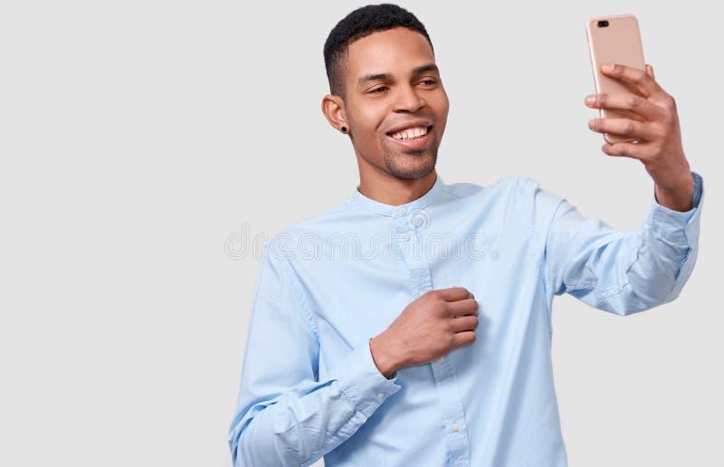 Человек Amerfican счастливого африканца молодой держит современный умный телефон, говорить онлайн и блоггинг на мобильном телефон стоковая фотография