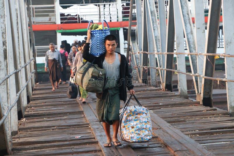 Человек Myanmese нося большую сумку 2 и взвалить корзину банана debark от корабля с много пассажиров идет за мостом стоковое изображение rf