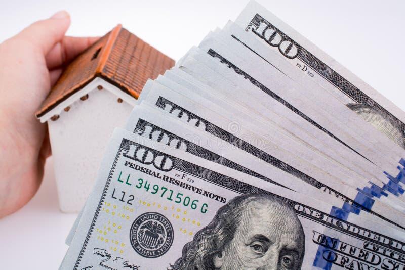 Человеческая рука держа модельный дом стороной aAmerican банкнот доллара стоковое изображение rf