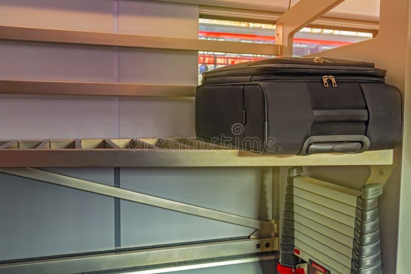 Чемодан черноты дороги на полке в быстроходном поезде Концепция перемещения поезда и транспорта груза предпосылка красит желтый ц стоковая фотография