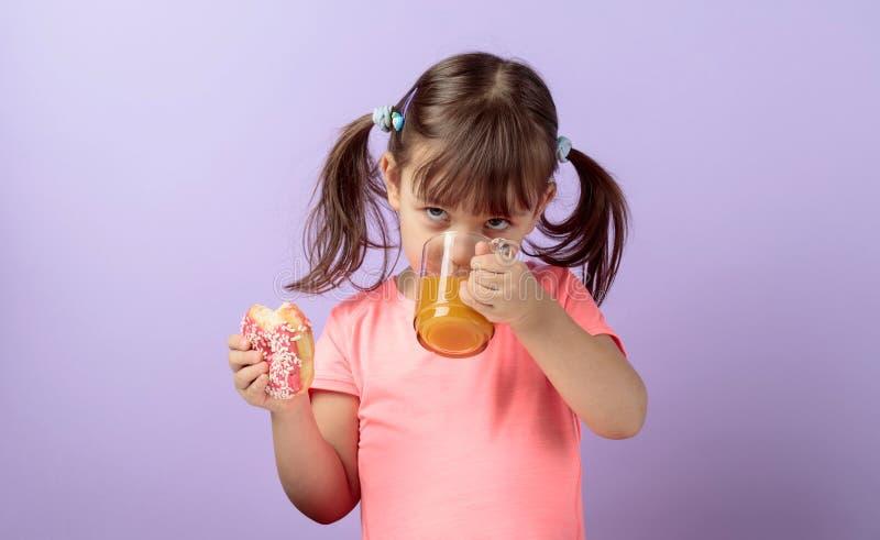 Четырехлетняя девушка в розовой футболке съесть донут и выпить сок стоковое изображение