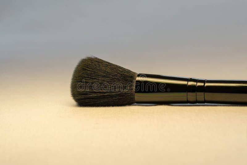 Черная щетка цвета лица макияжа на светлом конце предпосылки вверх по изображению Принципиальная схема заботы красоты и кожи стоковое фото rf