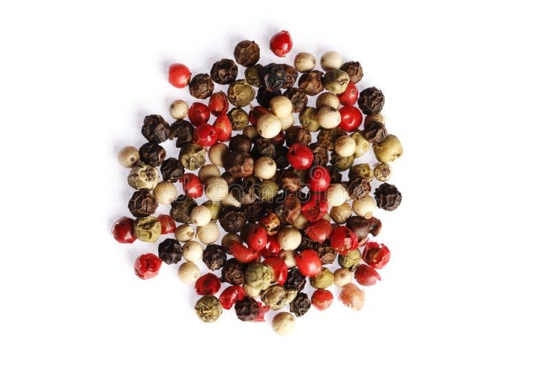 Черные белые и красные перцы изолированные на белой предпосылке стоковое фото