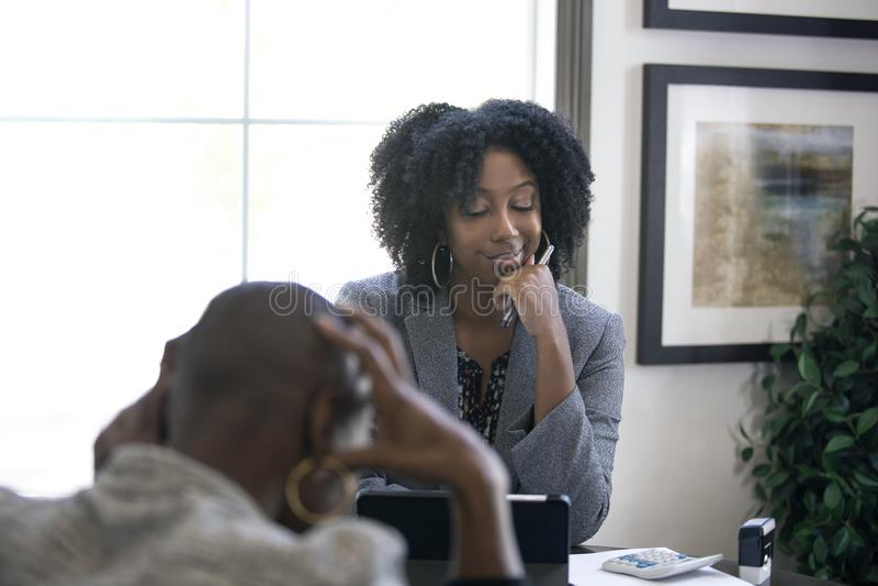 Черный женский клиент сердитый на бухгалтере налога CPA стоковая фотография