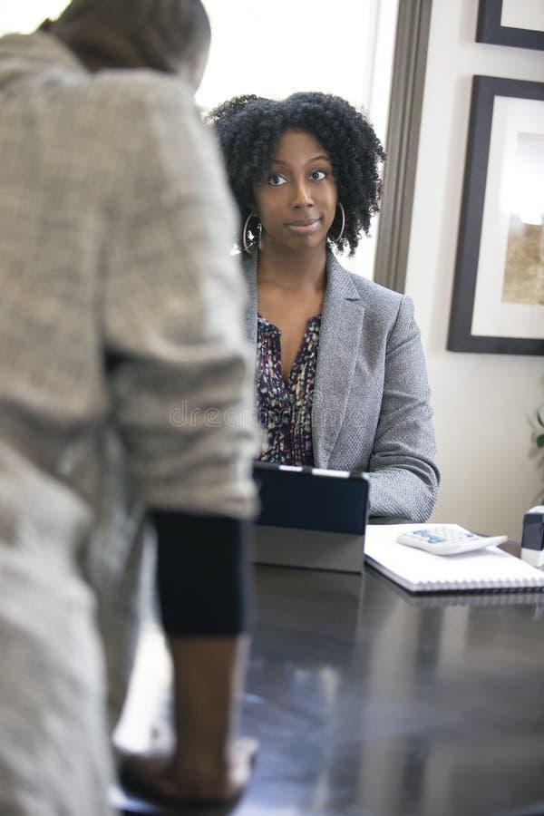 Черный женский клиент сердитый на бухгалтере налога CPA стоковое фото