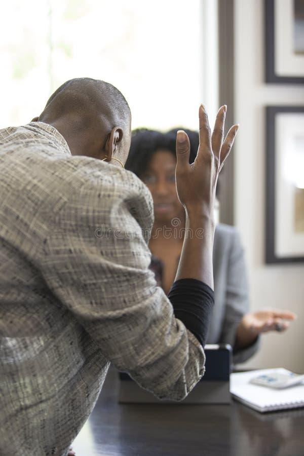 Черный женский клиент сердитый на бухгалтере налога CPA стоковое изображение