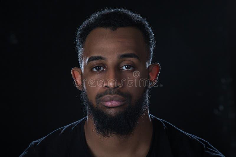 Чернокожий человек смотрит право на черную предпосылку с бородой и усиком стоковые изображения