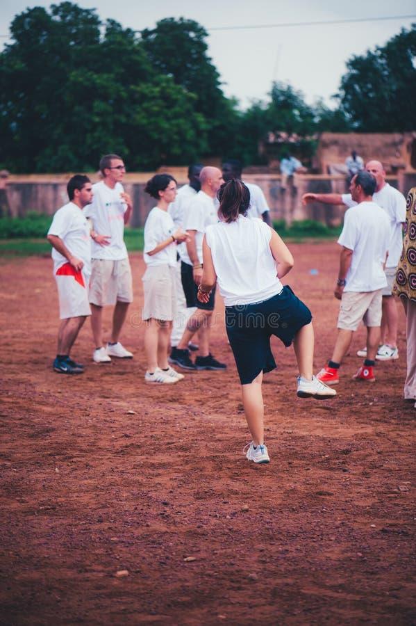 Черно-белые люди играя футбол в сельской африканской деревне стоковая фотография