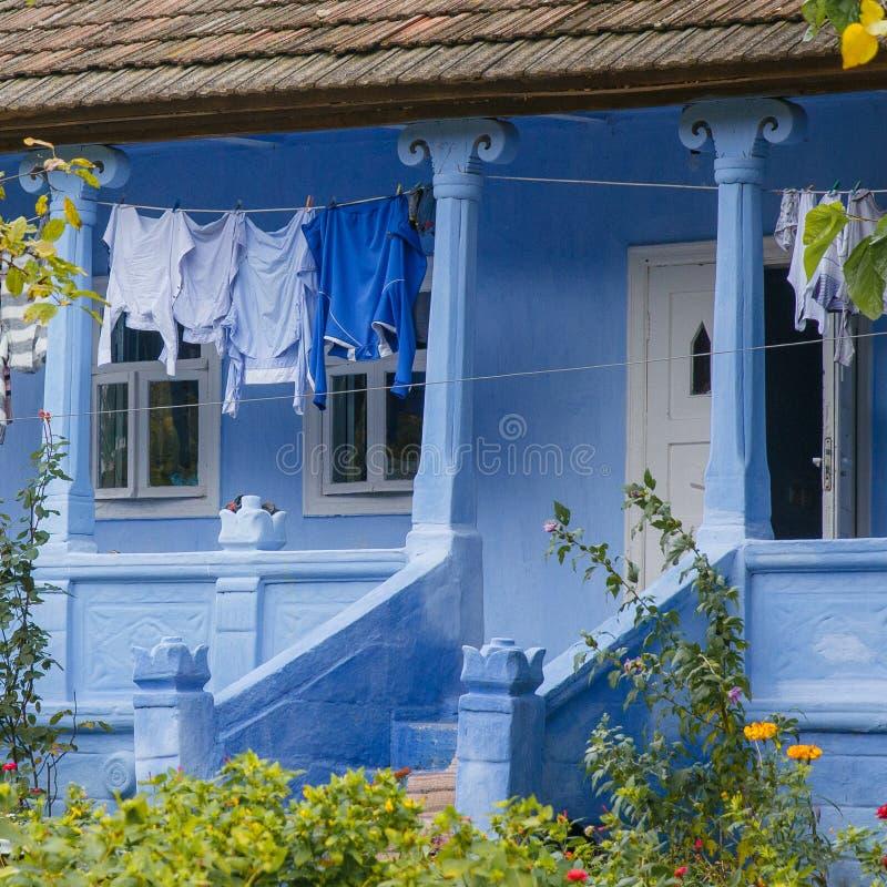 Чистые одежды высушены во дворе  голубого сельского дома стоковые фотографии rf