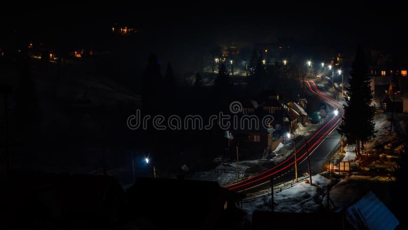 Чудесная панорама горного села ночи Украины со следами автомобиля стоковое фото