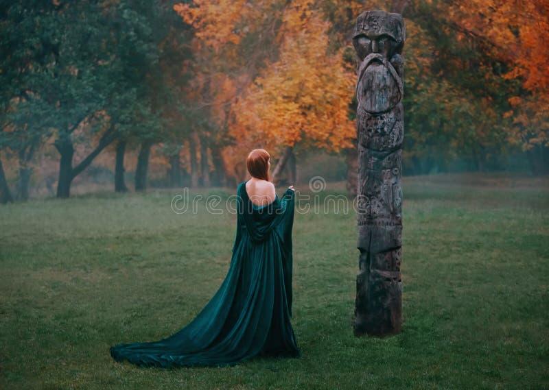 Чудесная девушка в длинном изумрудном платье шелка с обнаженными жизнями плеч в туманном лесе, приходит к освобождаться на холме  стоковое изображение