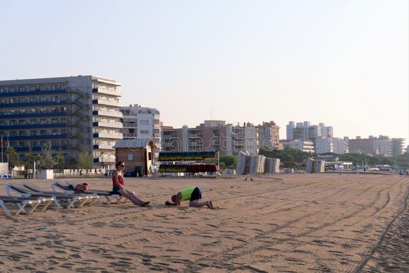 Херона, Испания, август 2018 Интересная сцена на пляже в Испании, человек умоляет прощению от его жены стоковая фотография rf