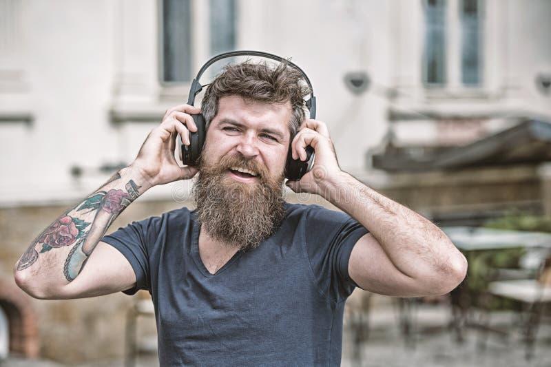 Хипстер наслаждается высококачественным звуком песни в наушниках Получите подписку музыки Насладитесь свободными песнями ежедневн стоковое фото