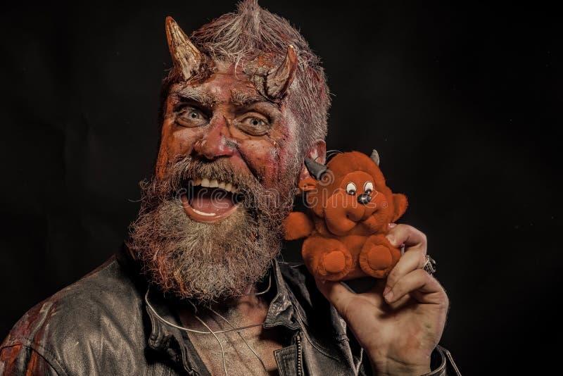 Хипстер хеллоуина с satan рожками, кровопролитные раны держит мягкое чудовище стоковые фотографии rf